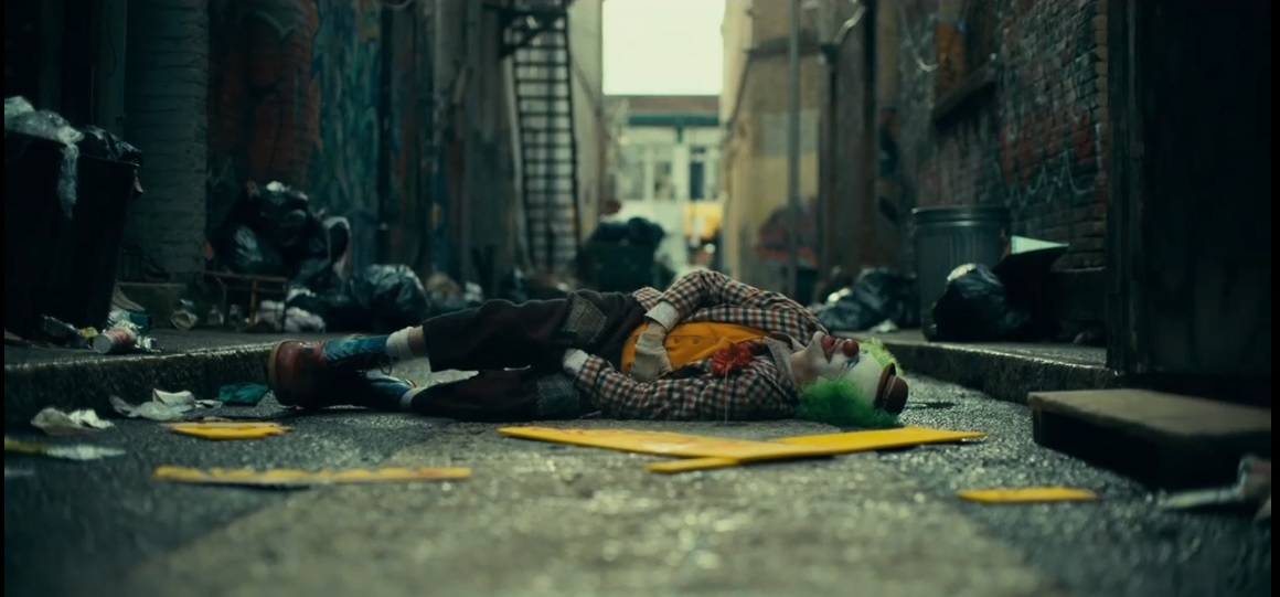 "alley scene from the film ""Joker"" where the main character Arthur Fleck, is seen lying on the pavement after being brutally beaten by a street gang."