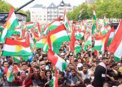 photo of a Kurdish political rally of thousands waving the flag of Kurdistan.