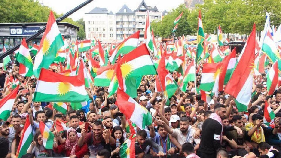 photo of a Kurdish political rally of thousands waving the flag of Kurdistan.