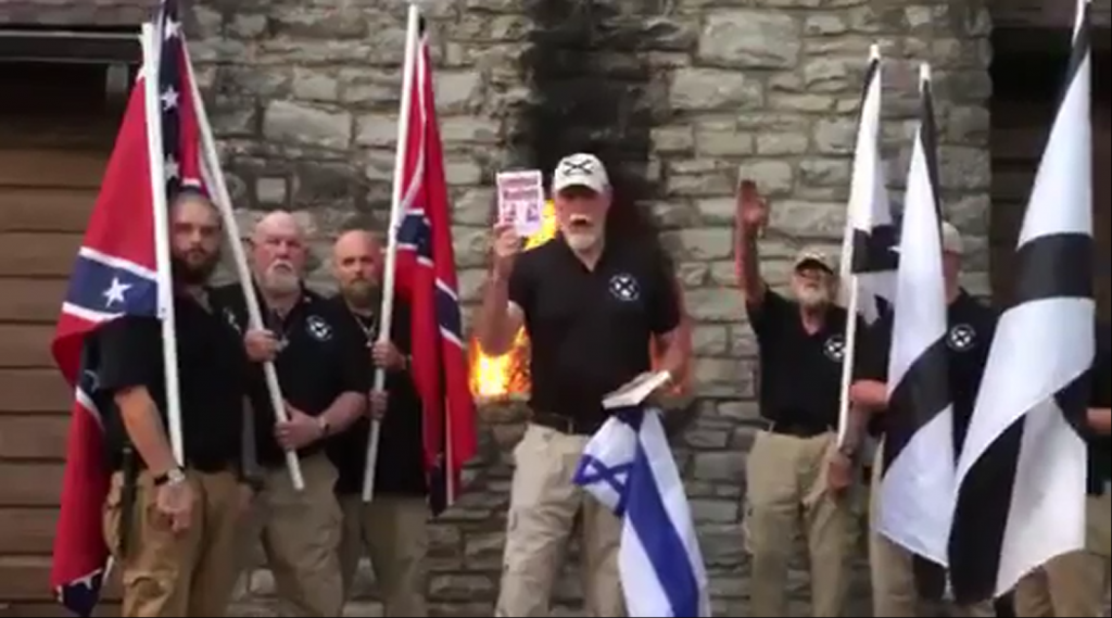 Co-founder of the League of the South, Michael Hill, burns an Israeli flag and the Talmud while members in the background hold Confederate Flags and give the Nazi salute. League members are openly supportive of Russian President Putin.