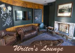 "photo of a room that has old, comfortable Leather upholstered couches, a fireplace, wood paneled walls, an Irish Whiskey advertisement, a wall mounted television and a vintage coffee table. The photo is dubbed, ""Writer's Lounge""."