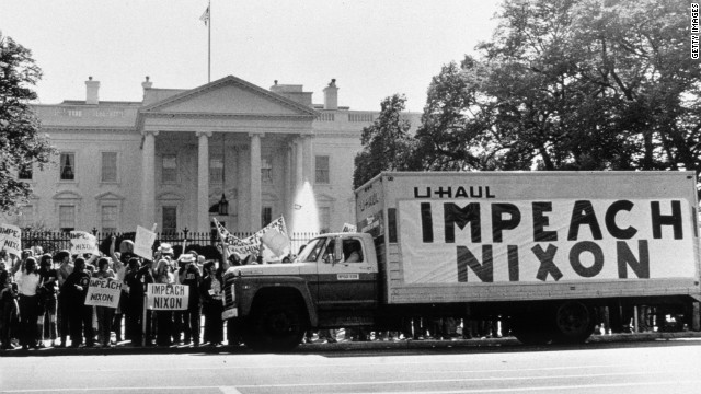 "Black and White period photo from 1973 of protesters outside the gates of the White House, holding signs saying ""Impeach Nixon"", together with a U-haul moving truck."