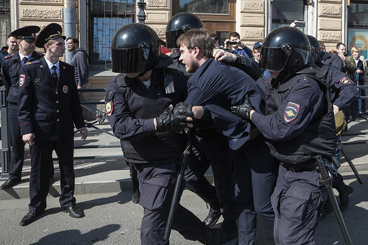 Police officers detain an opposition protester during a May Day rally in Saint Petersburg on May 1, 2019. - Police in Saint Petersburg on Wednesday broke up a sanctioned May Day opposition rally and detained more than 60 people after protesters chanted slogans critical of President Vladimir Putin, a monitor said.