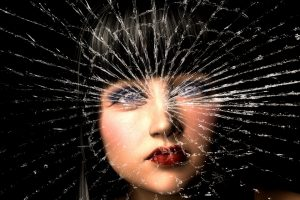 young woman's face behind shattered glass
