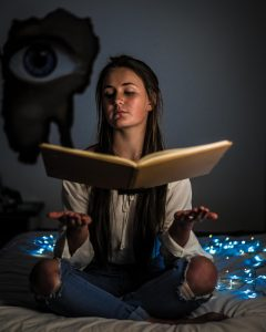 "Photo of ""new age"" girl with levitating book by Ivandrei Pretorius from Pexels"