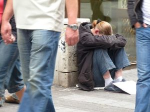 homeless young woman sitting with head lowered while people walk by