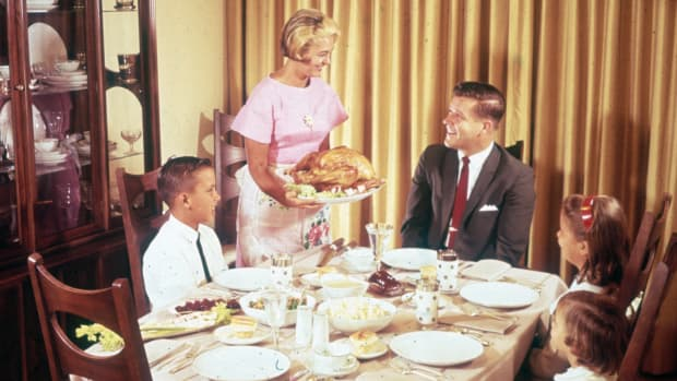 1960's era stock photo depicting the archtypical White suburban middle class family sitting down to Thanksgiving dinner