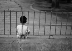 photo of a child aged 7 or 8, sitting in front of a wrought iron fence looking down towards an empty driveway.