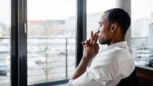 Depressed man looking out a window.