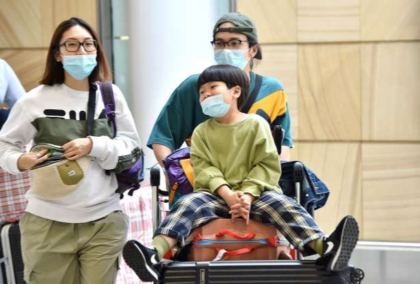 parents and child at Sydney International Airport, wearing N95 type flu prevention masks
