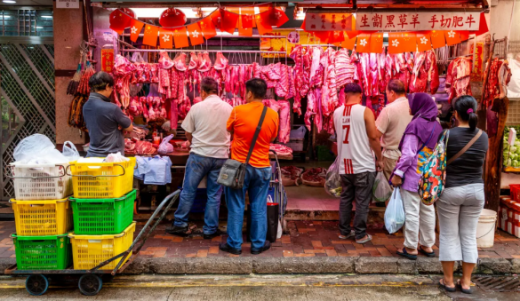 """photo of """"Wet Market"""" in Hong Kong, offering freshly slaughtered meat to customers by street vendors. Meat is not refrigerated when displayed."""