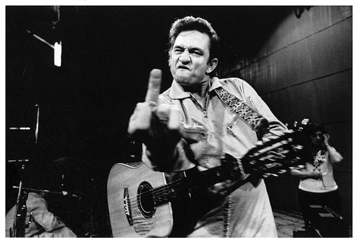 "iconic black and white photo of folk / country legend Johnny Cash giving ""the finger""."