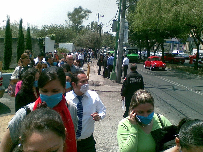 photo of busy main street with pedestrians donning virus protection masks as they walk along sidewalks.