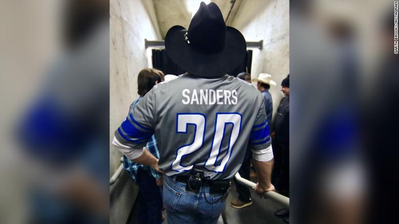"photo of Country music giant Garth Brooks wearing a Detroit Lions' player jersey with the name ""Sanders"" and the number ""20"" before a concert appearance at Detroit's Ford Field, home of the Lions football team."
