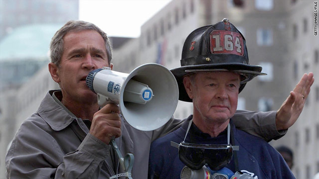 "photo of former president George W. Bush at ""Ground Zero"" - the rubble of the World Trade Center, addressing a crowd, using a ""bullhorn""."