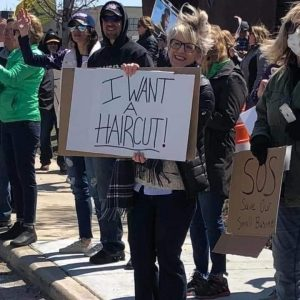 "Female protester holding a sign that says ""I want a haircut"""