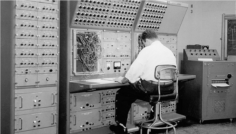 black and white photo, circa late 1960s of an IRS employee operating a massive mainframe computer operating on COBOL programming language