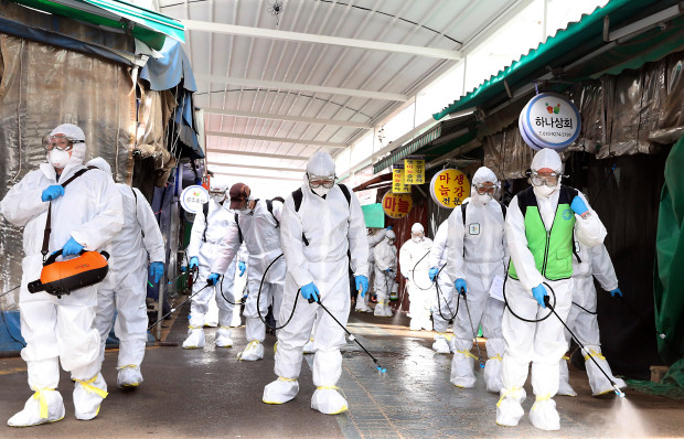 photo of South Korean disinfecting team, sanitizing a public space, wearing full Haz-Mat protective apparel