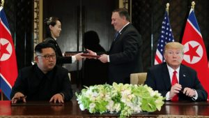 Kim Jong-un and President Trump seated at a table while Sec Pompeo hands a folder to Kim Yo-jong