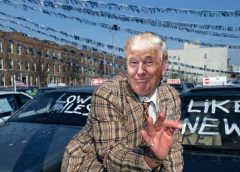 image of Donald Trump as sleazy used car salesman on a car lot.