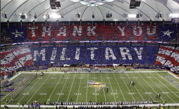 "photo of a staged patriotic display at an NFL game, with the audience having been given poster boards that when held up simultaneously, spell out the visualization, ""Thank You Military""."