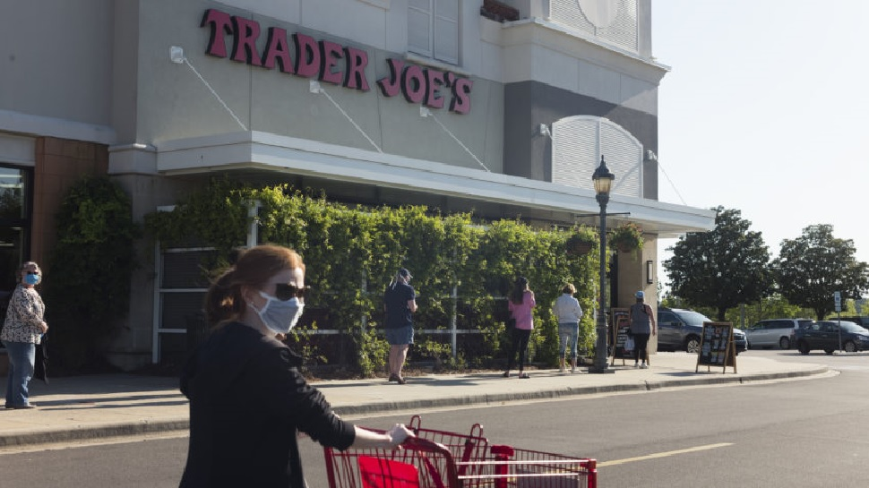 photo Trader Joe's retail location store front and shoppers wheeling carts in parking lot abiding by store policy of wearing protective face covering