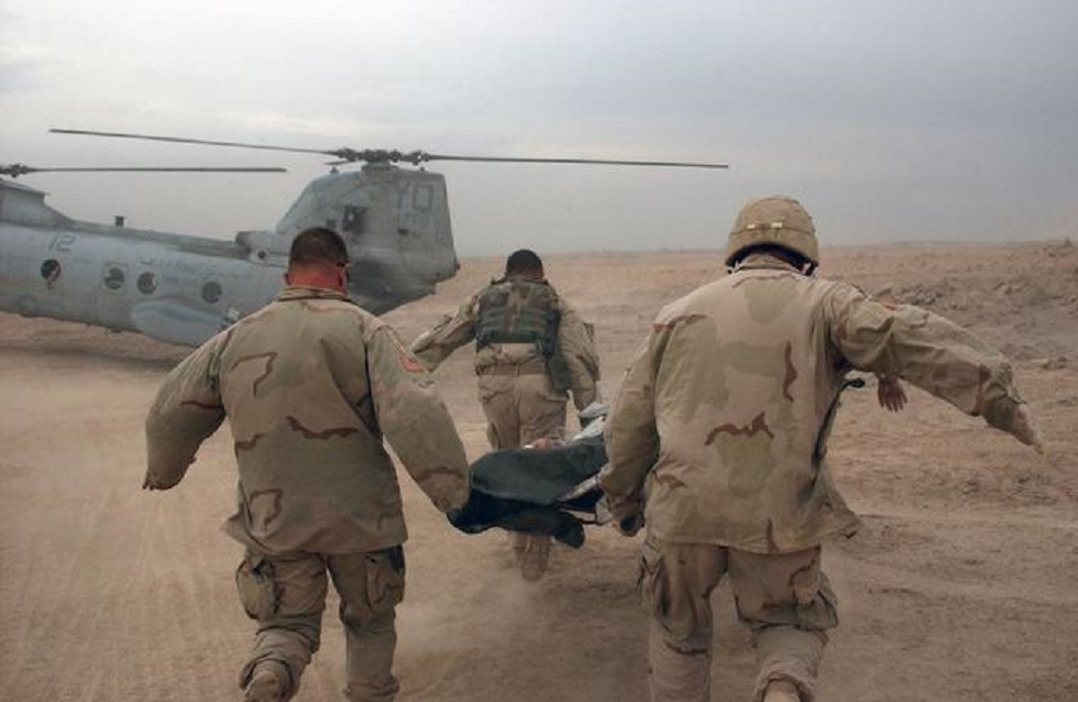 US Army (USA) Soldiers assigned to 2-7 Cavalry, 2nd Brigade Combat Team (BCT),3rd batt- 1st Division, rush a wounded Soldier from Apache Troop to a waiting US Marine Corps (USMC) CH-46E Sea Knight helicopter during operation in Fallujah, Iraq, during Operation IRAQI FREEDOM.