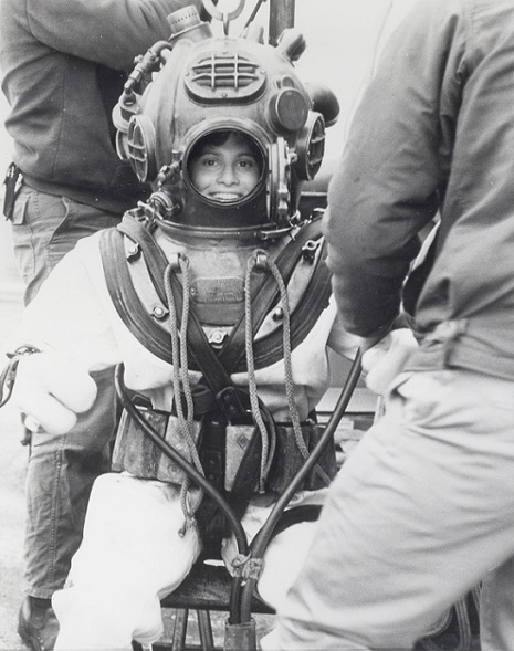 Female Deep Sea Diver being fitted in the diving suit and apparatus