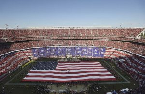 Aerial photograph of Levi's Stadium in Santa Clara, home to the San Francisco 49rs NFL franchise. The photo depicts a patriotic display with a large American flag unfurled across the playing field and another in the stands using coordinated placards, which assembled, suggest a flag motif.