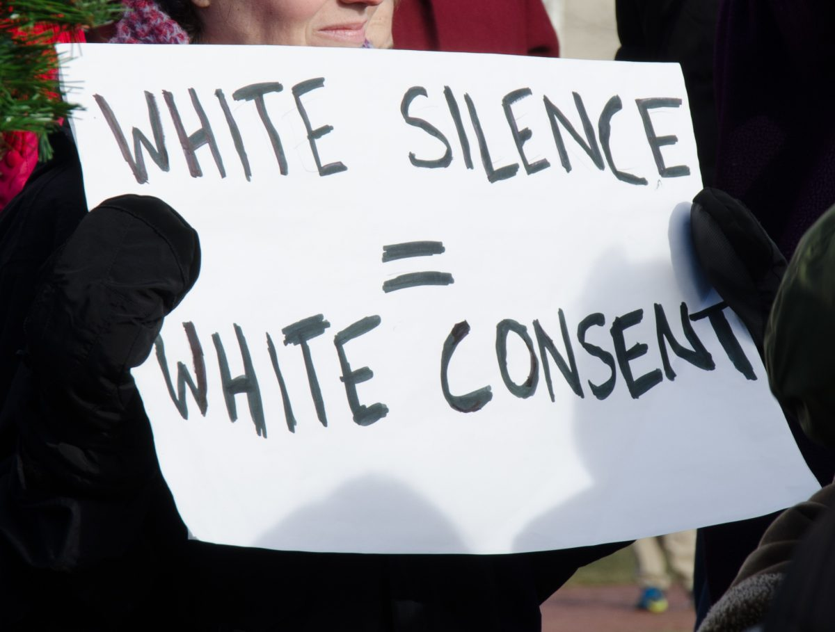 "photo of a protester's sign on White posterboard in Black marker, ""White Silence = White Consent"""