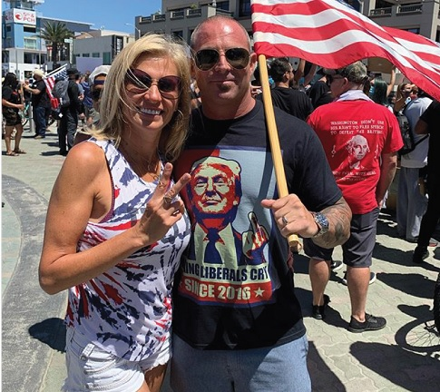 photo of Lenka Kolova, anti-COVID-19 mask activist and male companion at a COVID-19 denialist event, with a pro-Trump T-shirt and American flag in evidence.